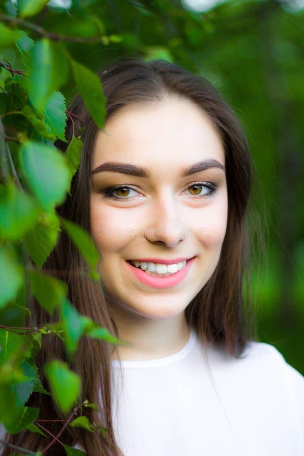 Porträt einer schönen jungen Frau auf einem Hintergrund von grünen Blättern, Sommer draußen Natürlich lächelnde Weile der Schönhe lizenzfreies stockbild