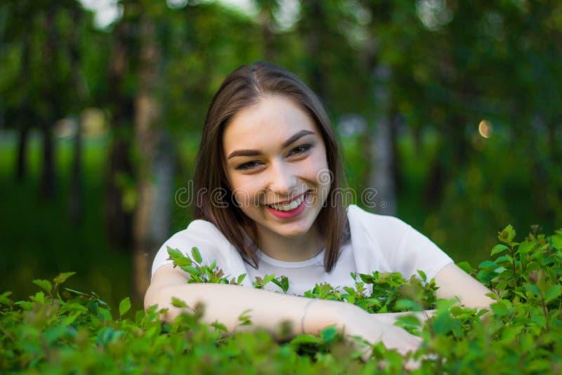 Porträt einer schönen jungen Frau auf einem Hintergrund von grünen Blättern, Sommer draußen Natürlich lächelnde Weile der Schönhe lizenzfreie stockbilder