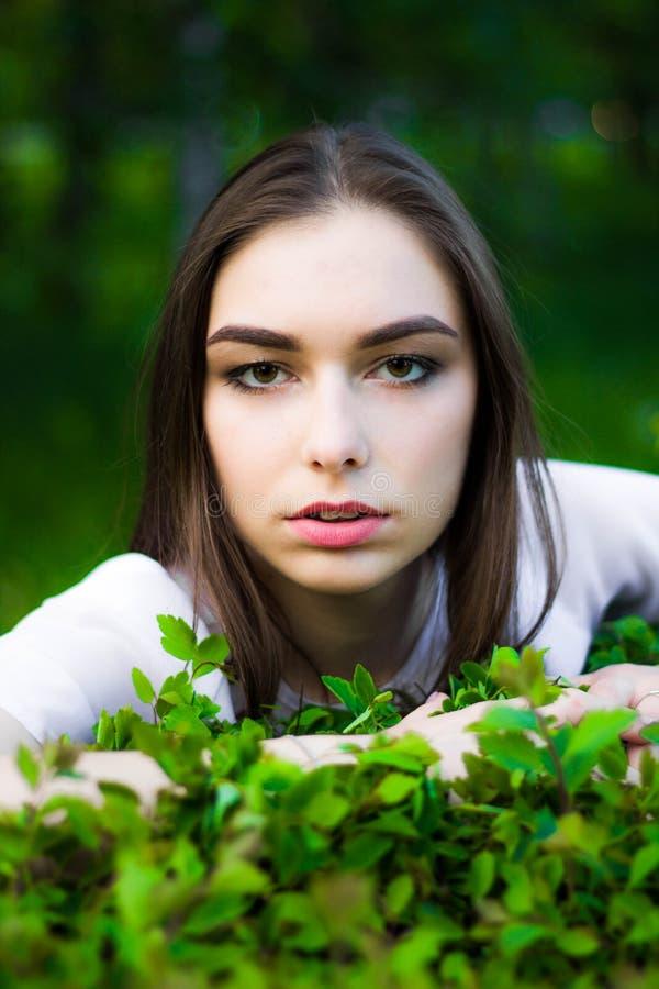 Porträt einer schönen jungen Frau auf einem Hintergrund von grünen Blättern, Sommer draußen Natürlich lächelnde Weile der Schönhe stockfoto