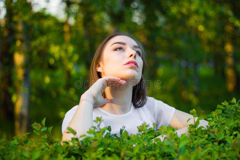 Porträt einer schönen jungen Frau auf einem Hintergrund von grünen Blättern, Sommer draußen Natürlich lächelnde Weile der Schönhe stockfotografie
