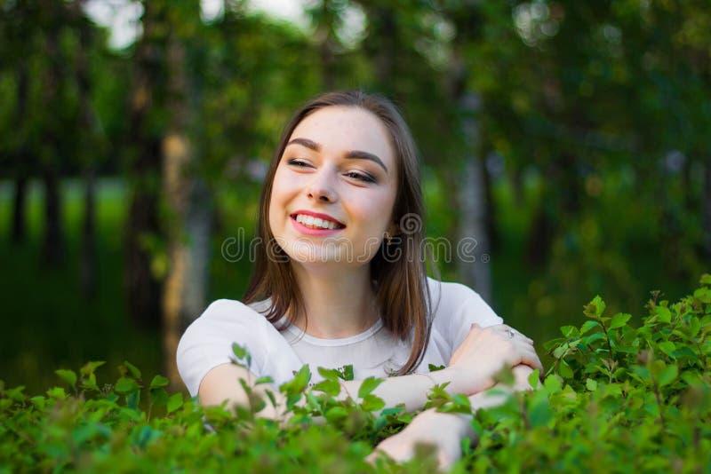 Porträt einer schönen jungen Frau auf einem Hintergrund von grünen Blättern, Sommer draußen Natürlich lächelnde Weile der Schönhe lizenzfreies stockfoto