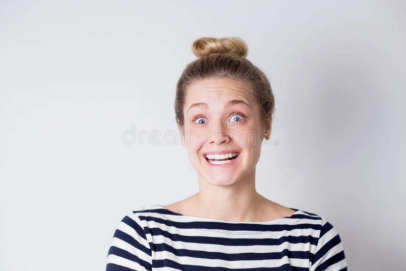 Porträt von lustigen netten lachenden und lächelnden Blondinen in gestreiftem Kleid auf weißem Hintergrund mit Kopienraum Junges  lizenzfreie stockfotos