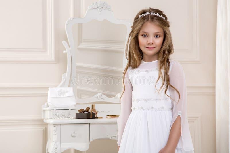 Porträt von nettem wenig Mädchen auf weißem Kleid und Kranz auf erstem Hintergrundkirchentor der heiligen Kommunion lizenzfreies stockbild