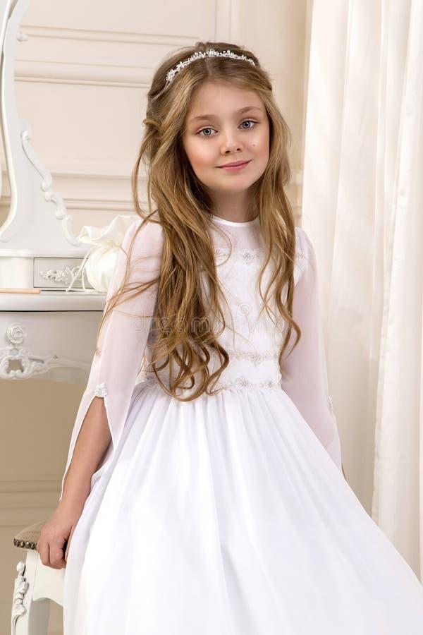 Porträt von nettem wenig Mädchen auf weißem Kleid und Kranz auf erstem Hintergrundkirchentor der heiligen Kommunion lizenzfreies stockfoto