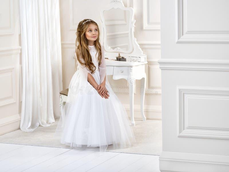 Porträt von nettem wenig Mädchen auf weißem Kleid und Kranz auf erstem Hintergrundkirchentor der heiligen Kommunion stockfoto
