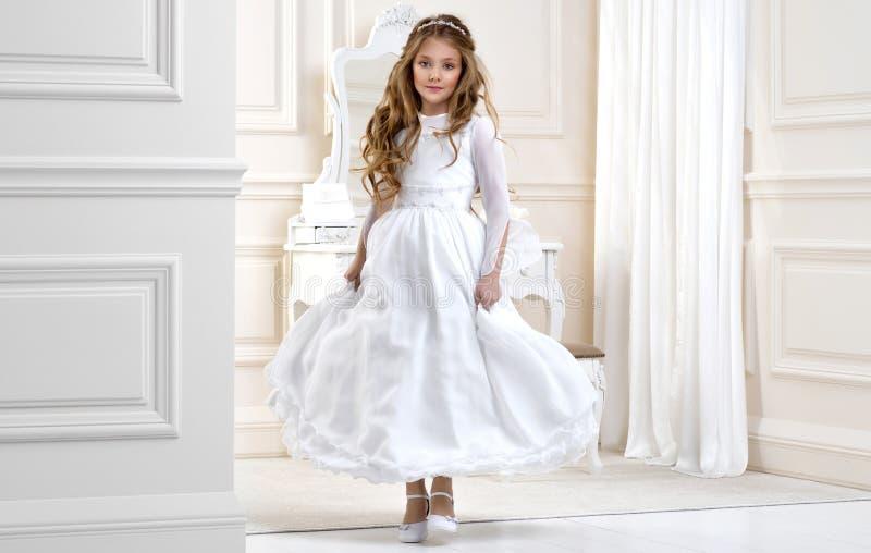 Porträt von nettem wenig Mädchen auf weißem Kleid und Kranz auf erstem Hintergrundkirchentor der heiligen Kommunion stockbilder