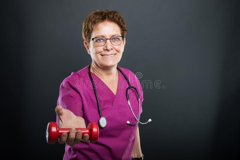 Porträt älteren Damendoktors, der einen Dummkopf anbietet stockfotografie