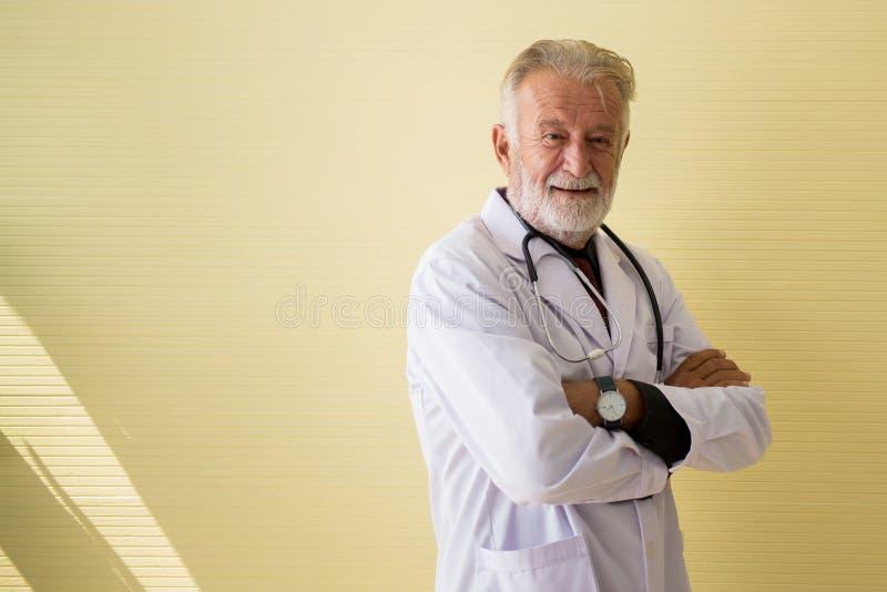 Porträt älterer Doktorstellung und Querder arme, die Kamera Krankenhaus-, glücklicher und positiverdenkender Haltung betrachten,  lizenzfreie stockbilder