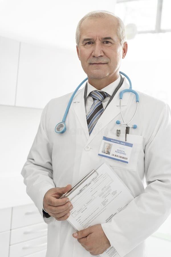 Porträt überzeugten älteren Doktors, der ärztliche Atteste über Klemmbrett an der Klinik liest stockfotos