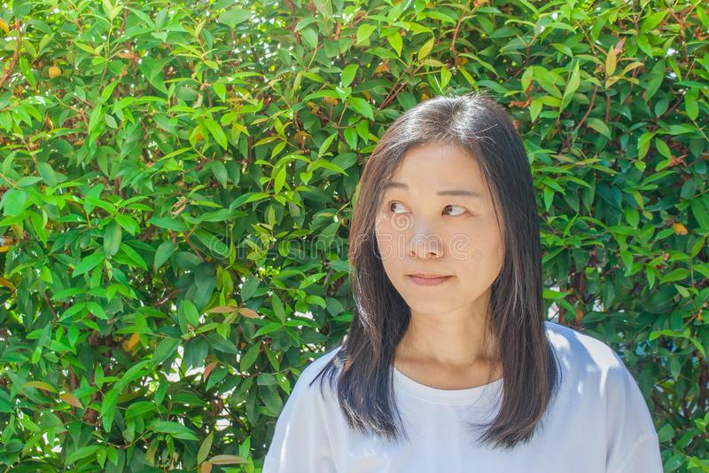 Porträt-Asiatin tragendes Whitt-shirt und Denken etwas Sie Hand der rechten Seite betrachtend lizenzfreies stockfoto