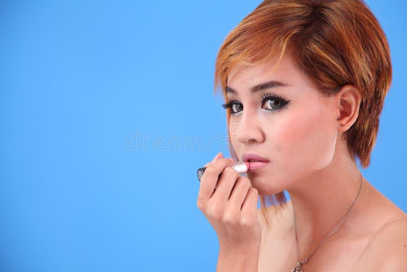 Porträt asiatischer Dame Lippenstift anwendend lizenzfreie stockbilder