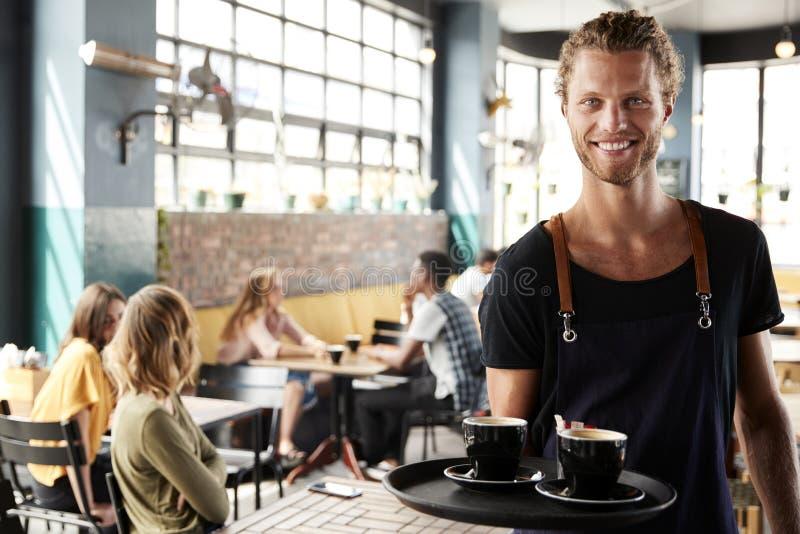 Porträt beschäftigter Kaffeestube Kellner-Serving Customers Ins lizenzfreie stockfotos