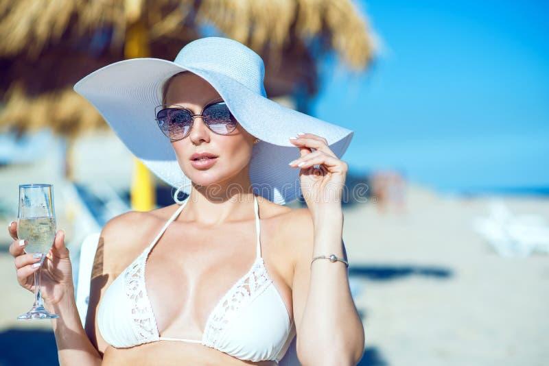 Porträt bezaubernder Dame im weißen Schwimmen-BH, im breitrandigen Hut und in der Sonnenbrille, die auf dem Liege mit einem Glas  stockfotos
