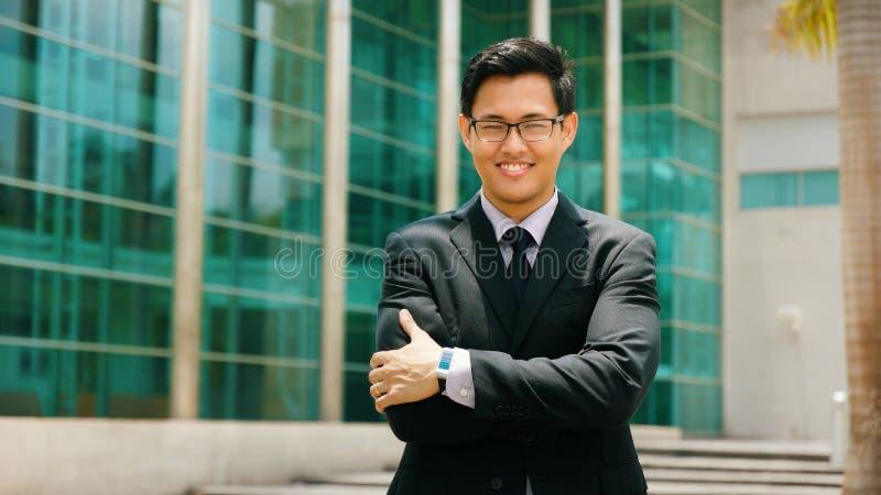 Porträt-chinesischer Geschäftsmann With Arms Crossed, das außerhalb O lächelt stockfoto