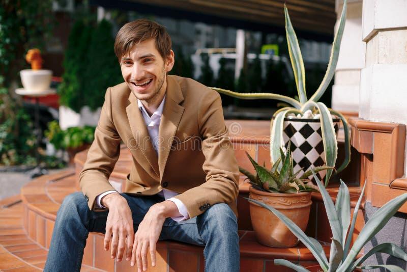 Porträt, das den jungen entspannten Mann draußen sitzt auf Weinlese lacht lizenzfreies stockbild