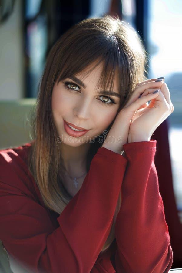 Portr?t, das junge Frau mit freundlichem L?cheln, l?chelndes Caf? des langen brunette Haares bezaubert lizenzfreie stockbilder