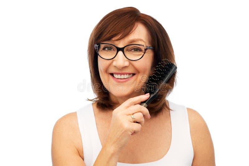 Porträt der älteren Frau in den Gläsern, die Haar bürsten stockfotos