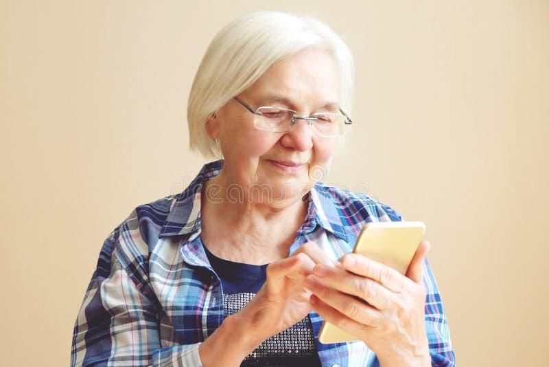 Porträt der älteren Frau, die Handy verwendet lizenzfreies stockfoto
