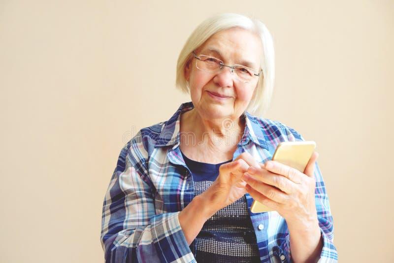 Porträt der älteren Frau, die zu Hause Handy verwendet stockfotografie