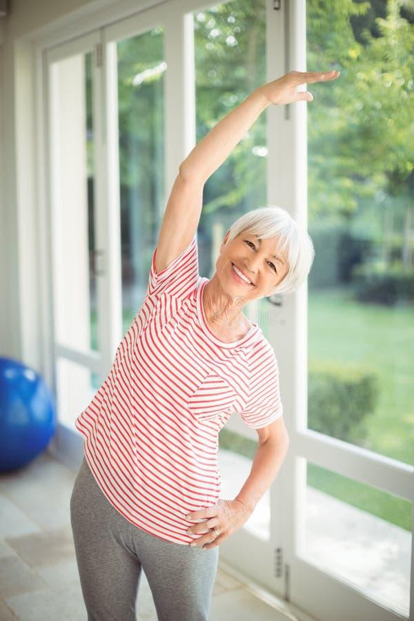 Porträt der älteren Frau durchführend, Übung zu Hause ausdehnend lizenzfreie stockbilder