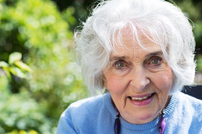 Porträt der älteren Frau entspannend im Garten lizenzfreies stockbild