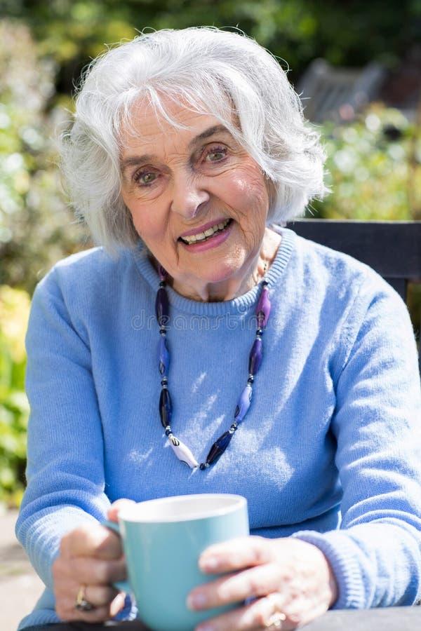Porträt der älteren Frau entspannend im Garten mit heißem Getränk stockfoto