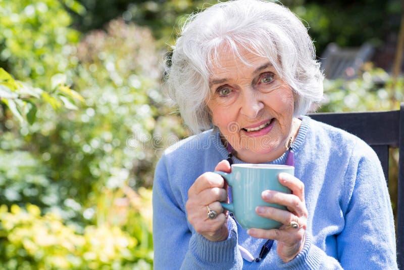 Porträt der älteren Frau entspannend im Garten mit heißem Getränk stockfotografie