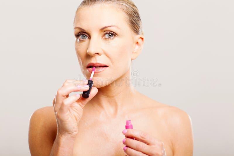 Ältere Frau, die Lippenglanz setzt stockfotos