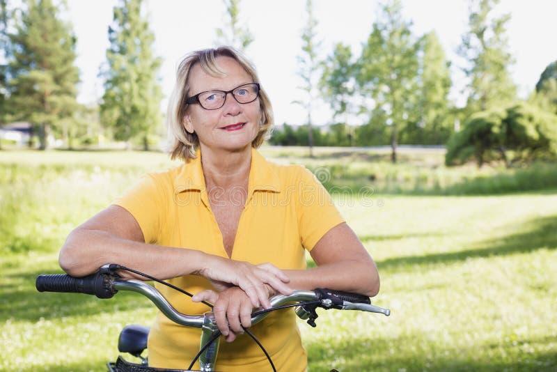 Porträt der älteren Frau mit einem Fahrrad, das eine Pause macht stockfoto
