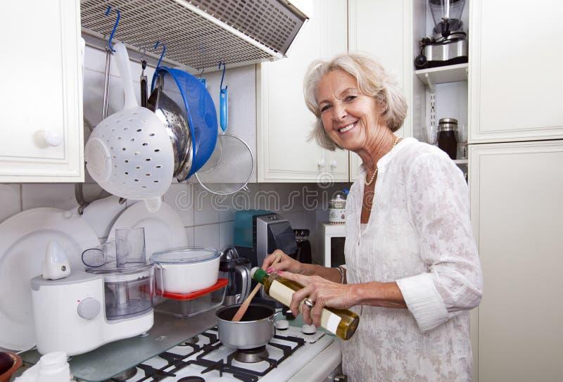 Porträt der älteren Frau Olivenöl Kasserolle an der Küchenarbeitsplatte hinzufügend lizenzfreie stockfotografie