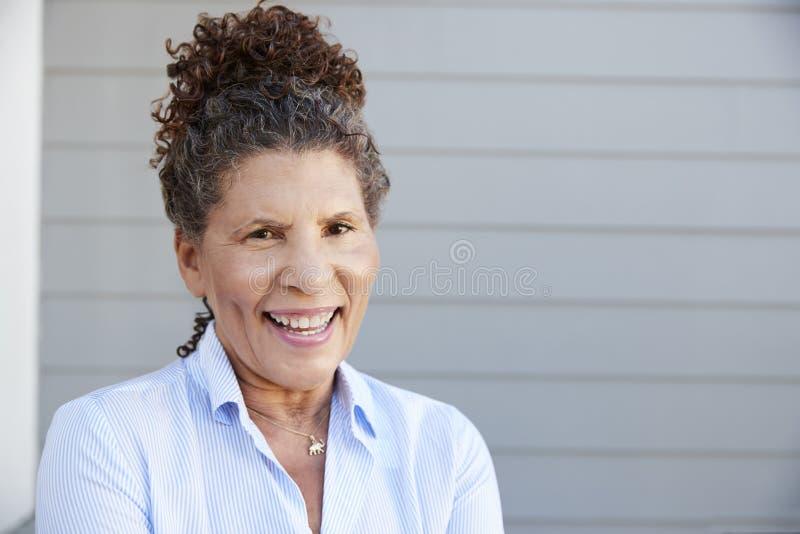 Porträt der älteren Frau stehendes externes Grey Clapboard House stockbilder