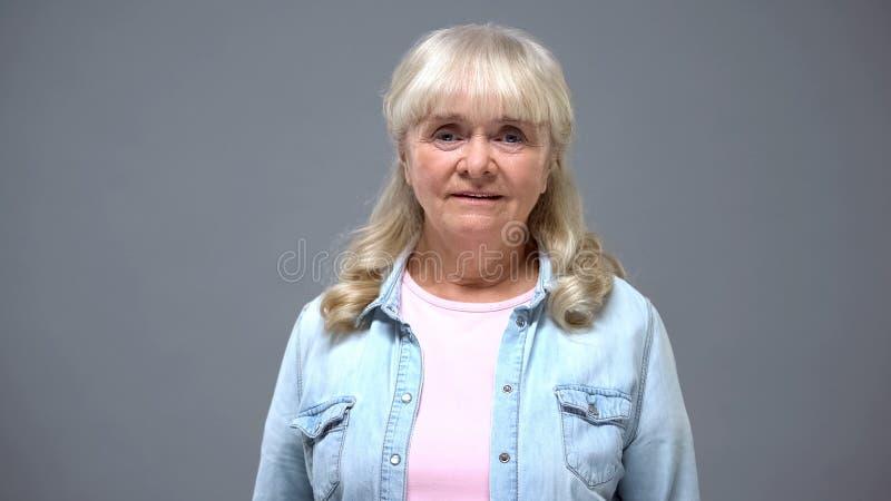 Porträt der älteren Frau in der zufälligen Kleidung lokalisiert auf Grauem, Pensionsalter stockbilder
