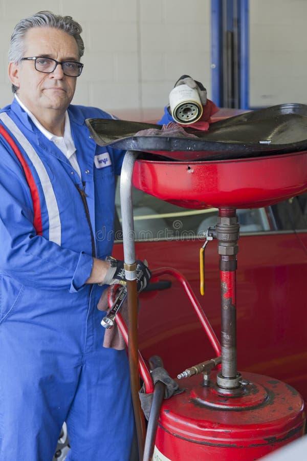 Porträt der älteren Mechanikerstellung außer Autosprühfarbeausrüstung stockfotos