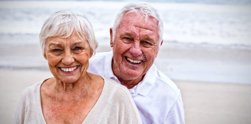 Porträt der älteren Paarstellung auf dem Strand lizenzfreie stockfotos