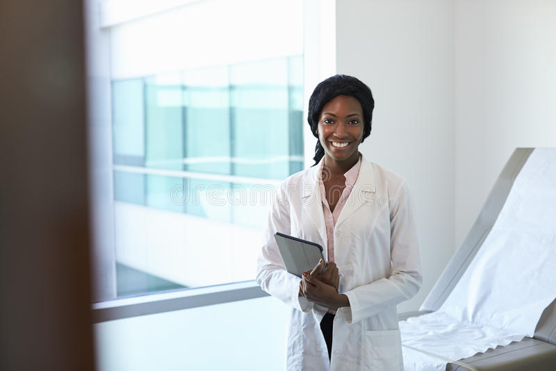 Porträt der Ärztin With Digital Tablet im Prüfungs-Raum stockfotografie