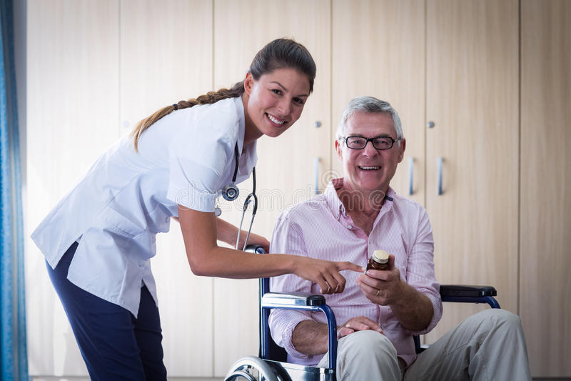 Porträt der Ärztin Medizin gebend dem älteren Mann lizenzfreie stockfotografie