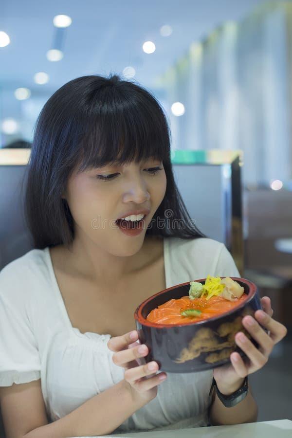 Porträt der überraschten jungen asiatischen Frau, die japanische Nahrung hält lizenzfreies stockbild