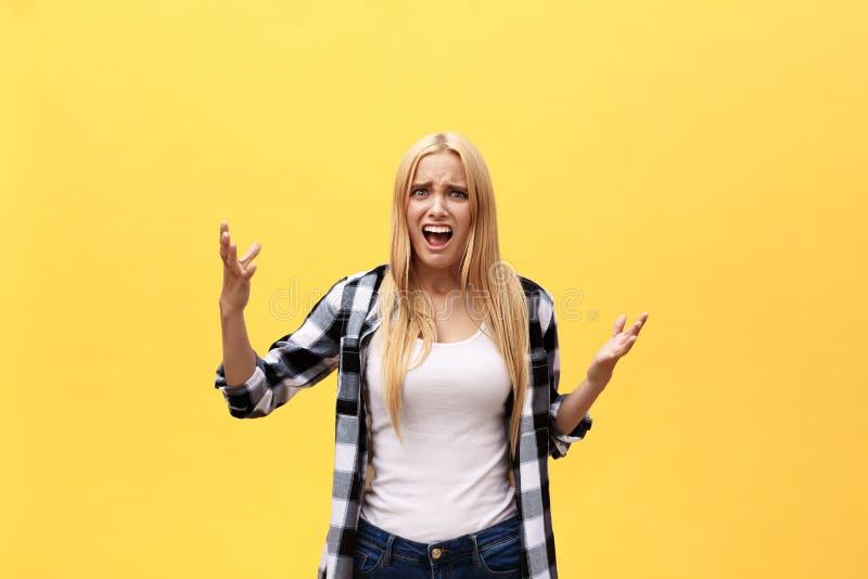 Porträt der überraschten jungen Frau in der weißen Hemdstellung vor gelber Wand lizenzfreies stockbild