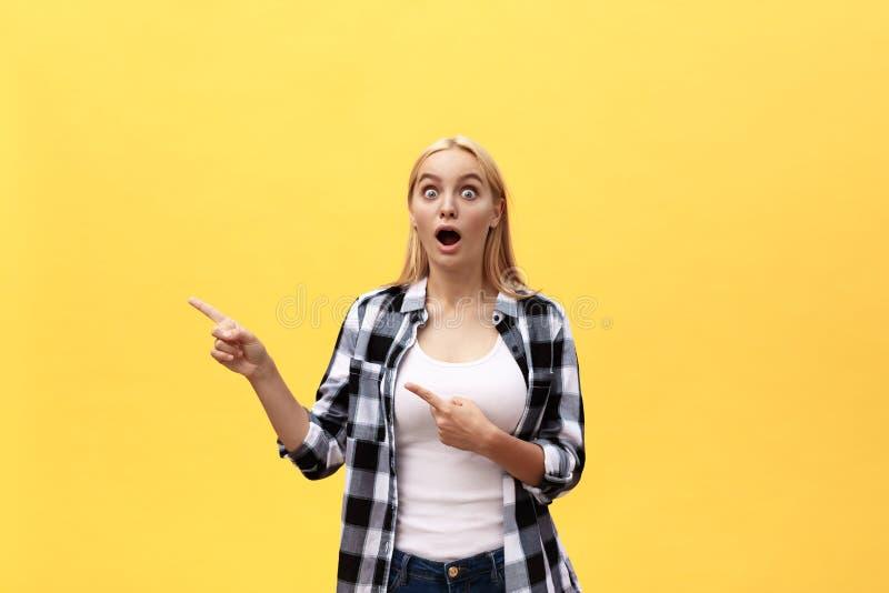 Porträt der überraschten jungen Frau in der weißen Hemdstellung vor gelber Wand lizenzfreie stockbilder