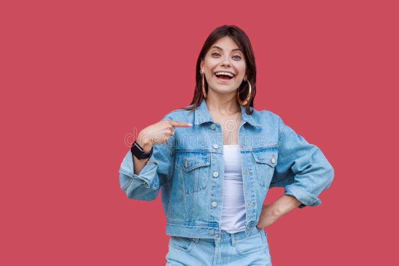 Porträt der überraschten schönen brunette jungen Frau mit Make-up in der Stellung der zufälligen Art des Denims, zeigend und betr lizenzfreie stockfotografie