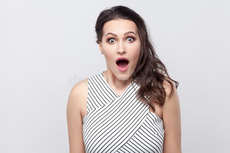 Porträt der überraschten schönen jungen brunette Frau mit Make-up und gestreifter Kleiderstellung, Kamera mit den großen Augen be stockbilder