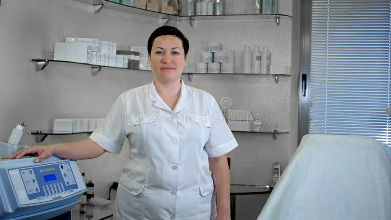 Porträt der überzeugten Ärztin stehend im Laborkittel, Kamera betrachtend lizenzfreie stockfotos