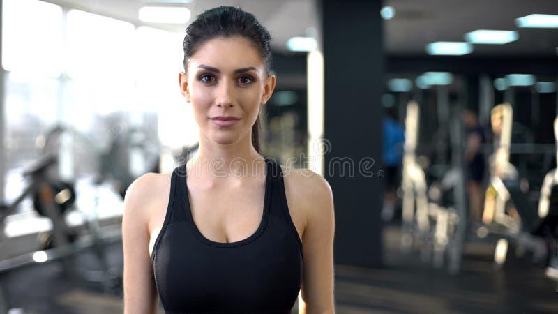 Porträt der überzeugten jungen Frau in der Turnhalle, die Kamera, persönlicher Trainer untersucht lizenzfreie stockfotografie