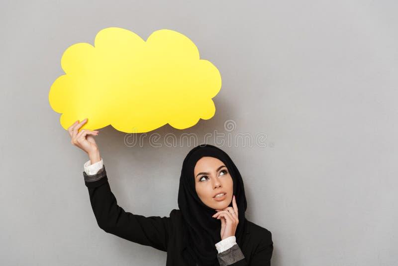 Porträt der arabischen jungen Frau in schwarzem traditionellem hijab holdin lizenzfreie stockbilder
