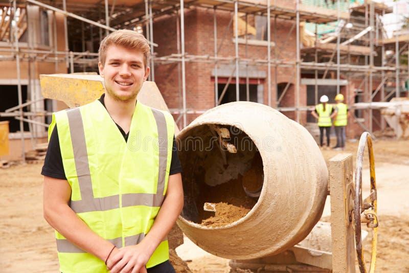 Porträt der Arbeitskraft auf Baustelle-mischendem Zement lizenzfreie stockbilder
