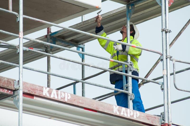 Porträt der Arbeitskraft auf Gestell auf Baustelle des konkreten Gebäudes lizenzfreies stockbild
