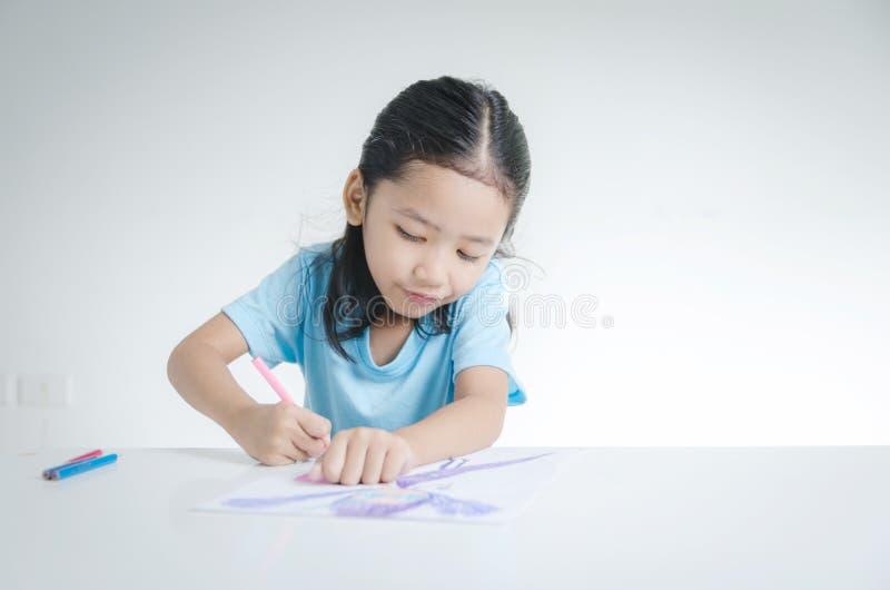 Porträt der asiatischen Zeichnung des kleinen Mädchens des Lächelns mit Farbbleistift stockfotografie
