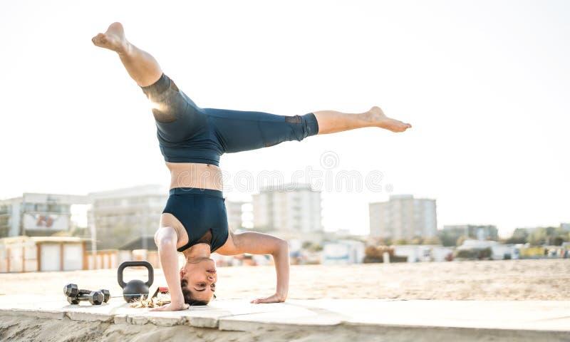 Porträt der athletischen Frau calisthenic Balancenbewegung am Freienstrandstandort ausübend - moderne Alternative ausarbeiten lizenzfreies stockfoto