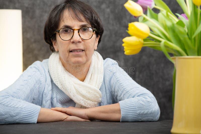 Porträt der attraktiven älteren brunette Frau mit dem Glassitzen stockfoto