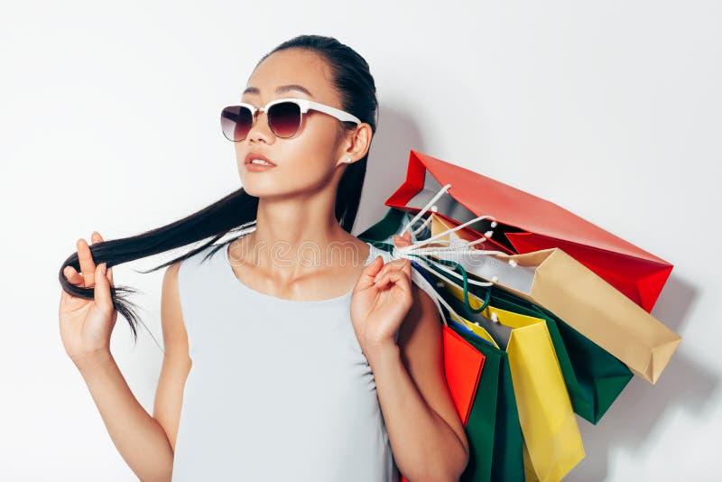 Porträt der attraktiven Asiatin in der Sonnenbrille und im Einkaufsba lizenzfreie stockfotos